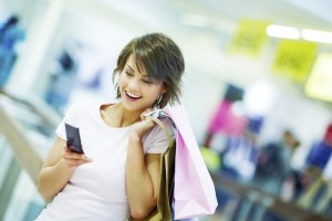 Portrait of a surpurised young woman holding a mobile and shopping bags